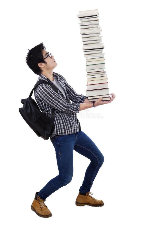 Hombre que lleva una pila de libros fotografía de archivo