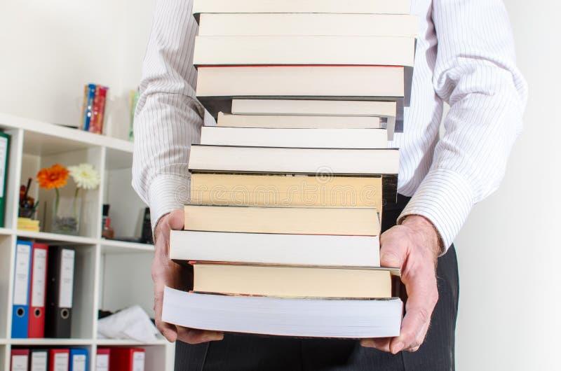 Hombre que lleva una pila de libros fotografía de archivo libre de regalías