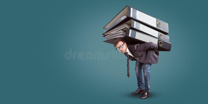 Hombre que lleva una pila gigante de carpetas fotografía de archivo libre de regalías