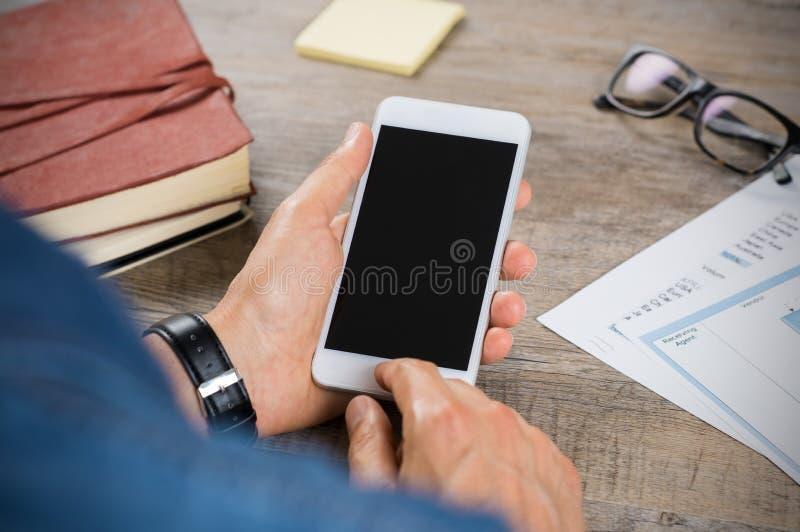 Hombre que manda un SMS en el teléfono fotos de archivo