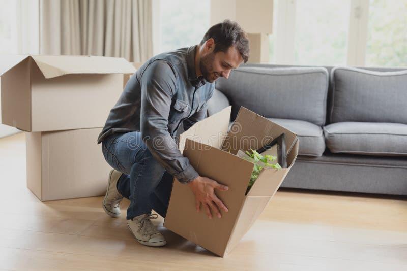 Hombre que mantiene abajo de la caja de cartón nuevo hogar imagen de archivo