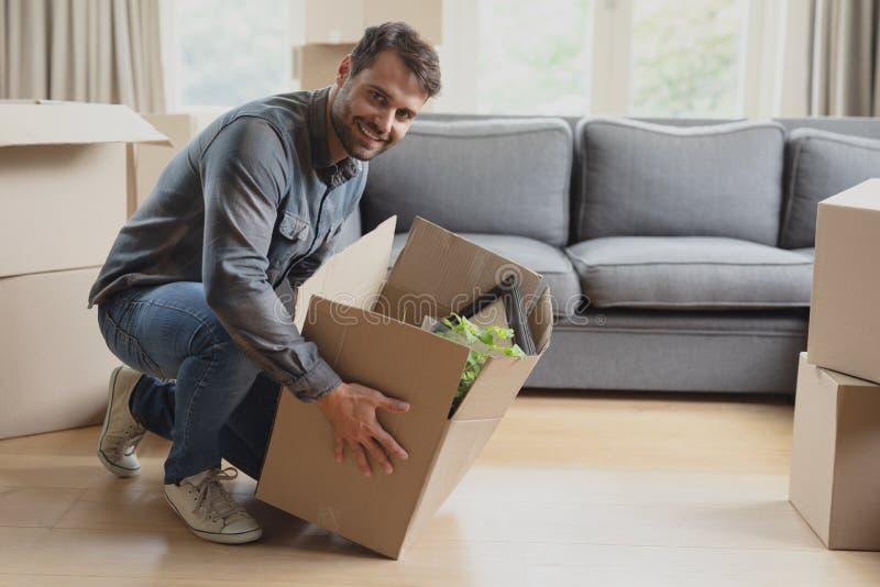 Hombre que mantiene abajo de la caja de cartón nuevo hogar foto de archivo libre de regalías