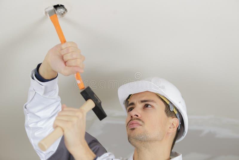 Hombre que martilla el techo concreto fotos de archivo