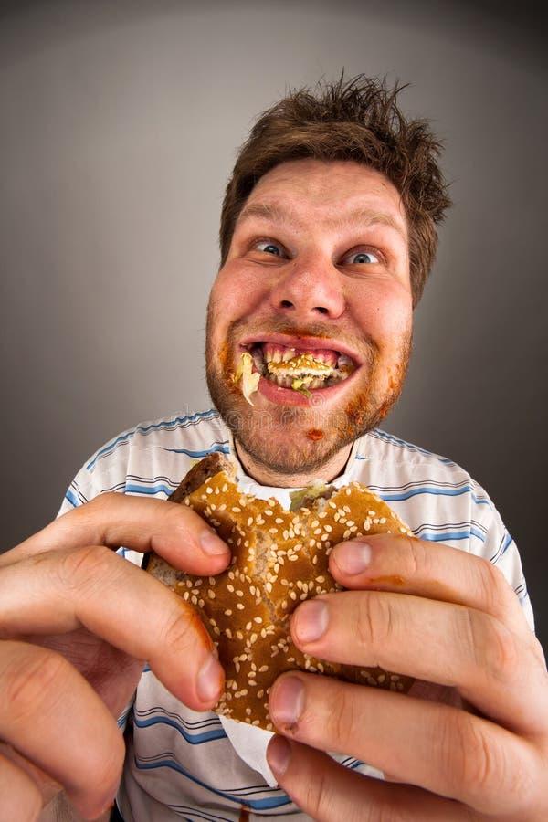 Hombre que mastica la hamburguesa fotos de archivo