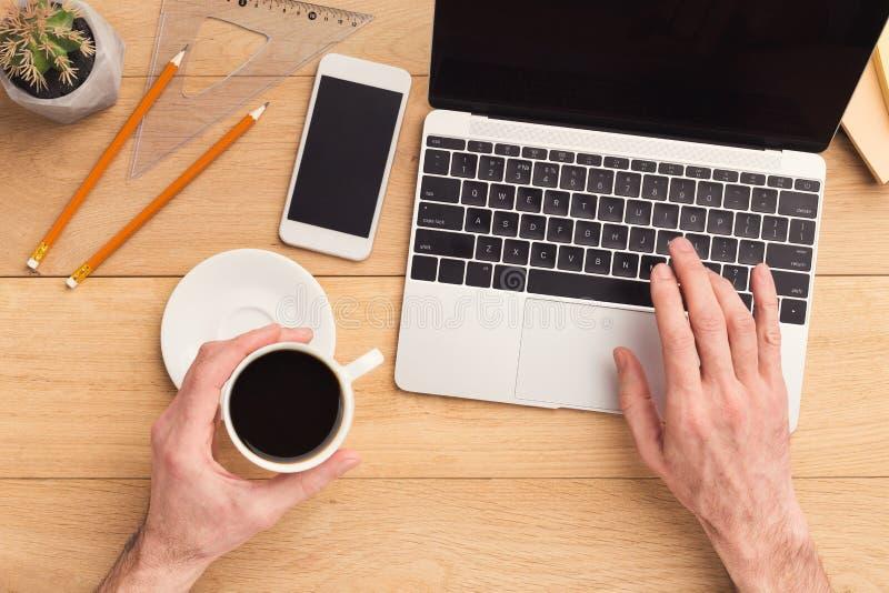 Hombre que mecanografía en el ordenador portátil en la tabla de madera foto de archivo libre de regalías