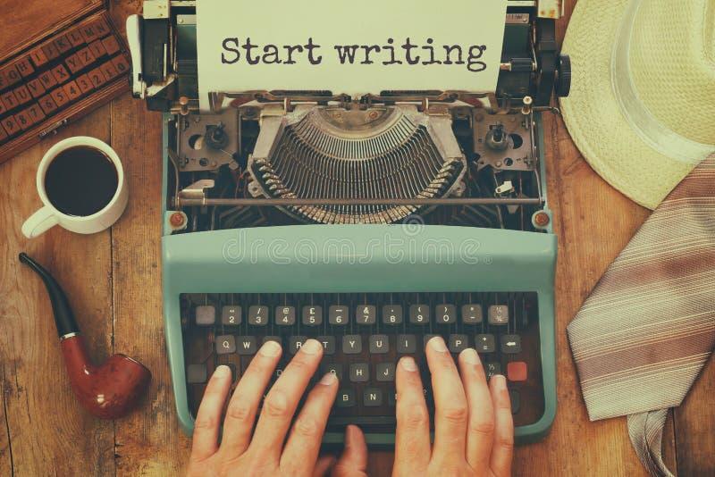 Hombre que mecanografía en la máquina de escribir del vintage con el texto: COMIENCE A ESCRIBIR imagenes de archivo