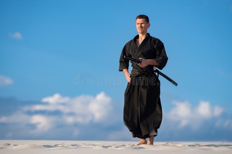 Hombre que medita antes de entrenar de los artes marciales fotos de archivo