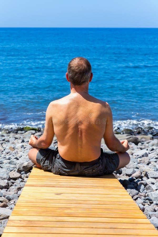 Hombre que medita en la playa y el mar fotos de archivo libres de regalías