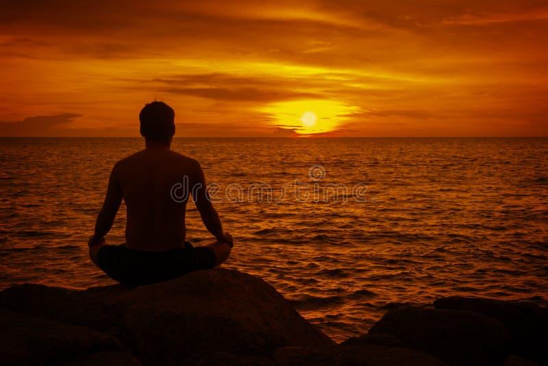 Hombre que medita en la puesta del sol. Playa tropical de Thaila imágenes de archivo libres de regalías