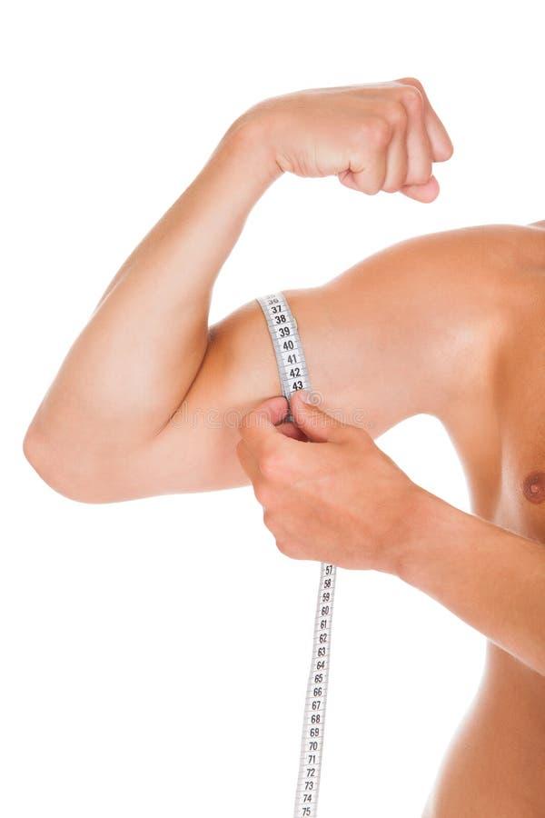 Hombre que mide su bíceps foto de archivo libre de regalías