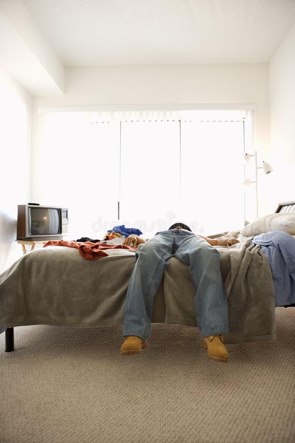 Hombre que miente en cama foto de archivo libre de regalías