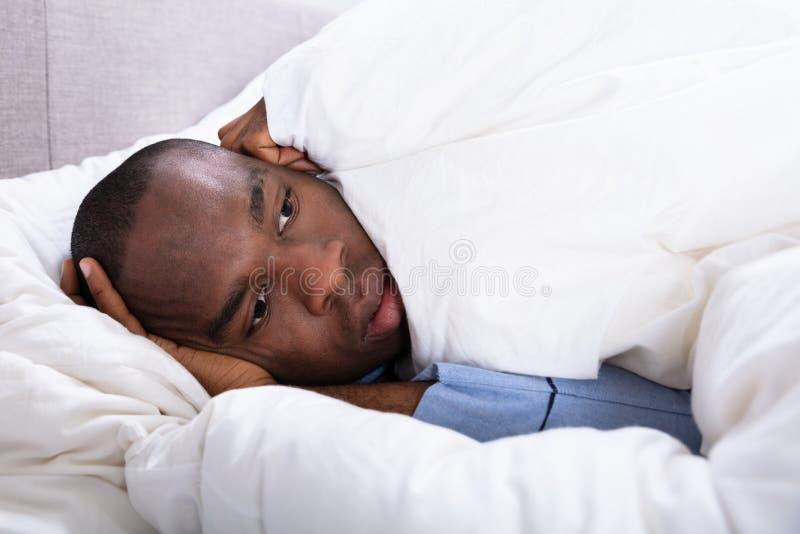 Hombre que miente en cama fotografía de archivo libre de regalías