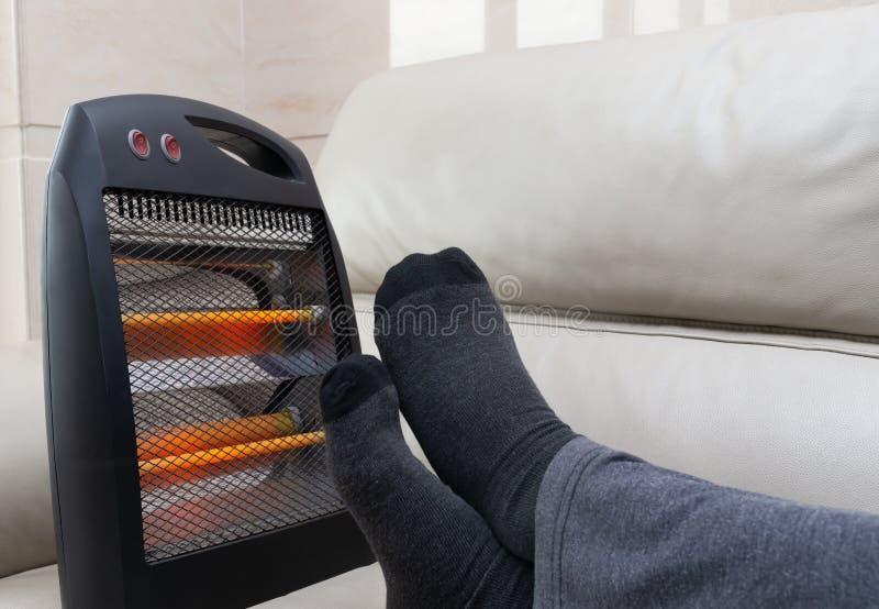 Hombre que miente en el sofá con el calentador eléctrico cerca de sus pies imagen de archivo libre de regalías