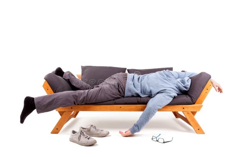 Hombre que miente en el sofá con resaca fotos de archivo