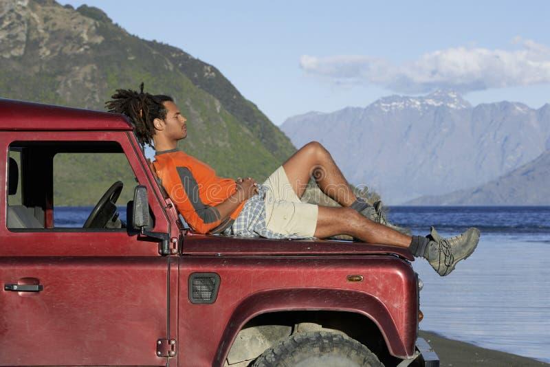 Hombre que miente en Jeep Hood By Mountain Lake fotos de archivo