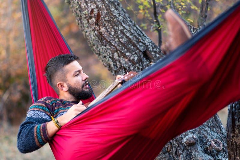 Hombre que miente en una hamaca y que se relaja al aire libre imagenes de archivo