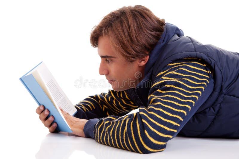 Hombre que miente leyendo un libro imágenes de archivo libres de regalías