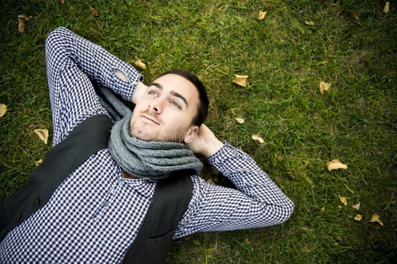 Hombre que miente sobre hierba verde imagenes de archivo