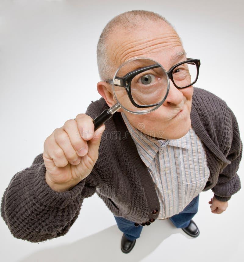 Hombre que mira con fijeza a través de la lupa imagen de archivo libre de regalías