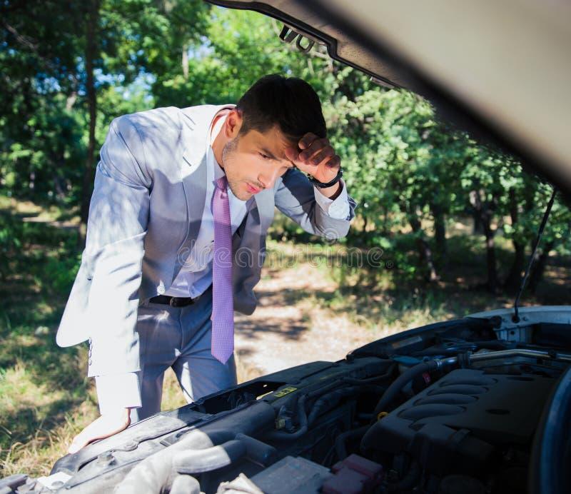 Hombre que mira debajo de la capilla del coche fotos de archivo