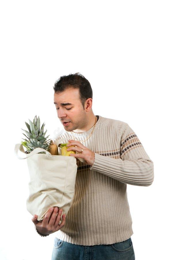 Hombre que mira dentro de su bolso de ultramarinos imagen de archivo libre de regalías