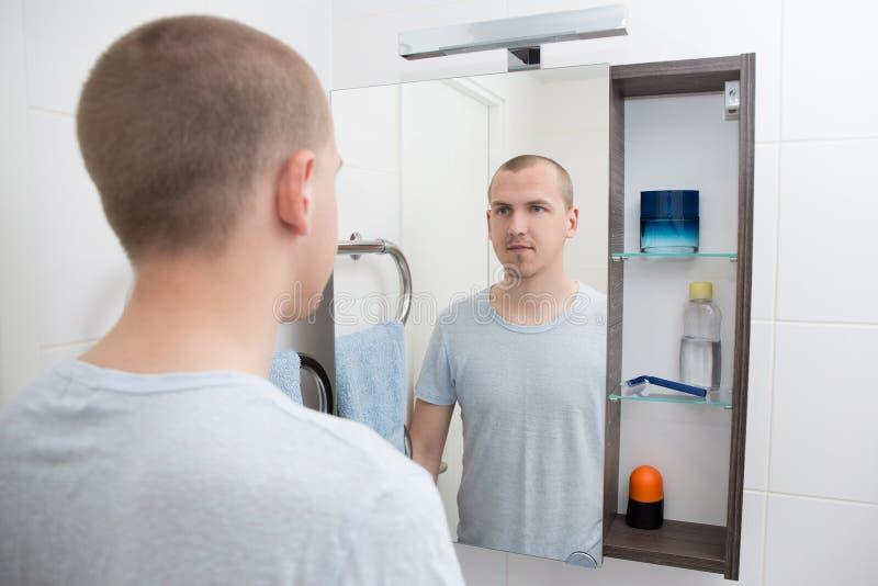 Hombre que mira el espejo en cuarto de baño fotografía de archivo libre de regalías