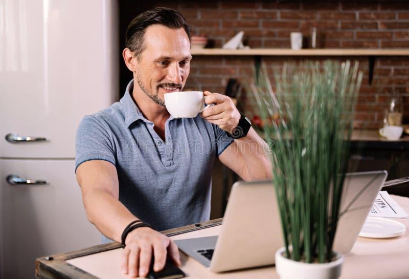 Hombre que mira el ordenador portátil en cocina fotos de archivo libres de regalías