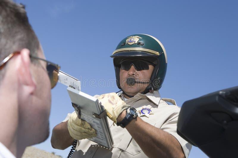 Hombre que mira el poli de tráfico que sostiene el tablero fotos de archivo libres de regalías