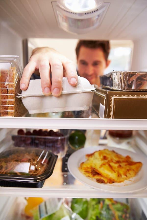 Hombre que mira el refrigerador interior llenado de la comida y que elige los huevos foto de archivo libre de regalías
