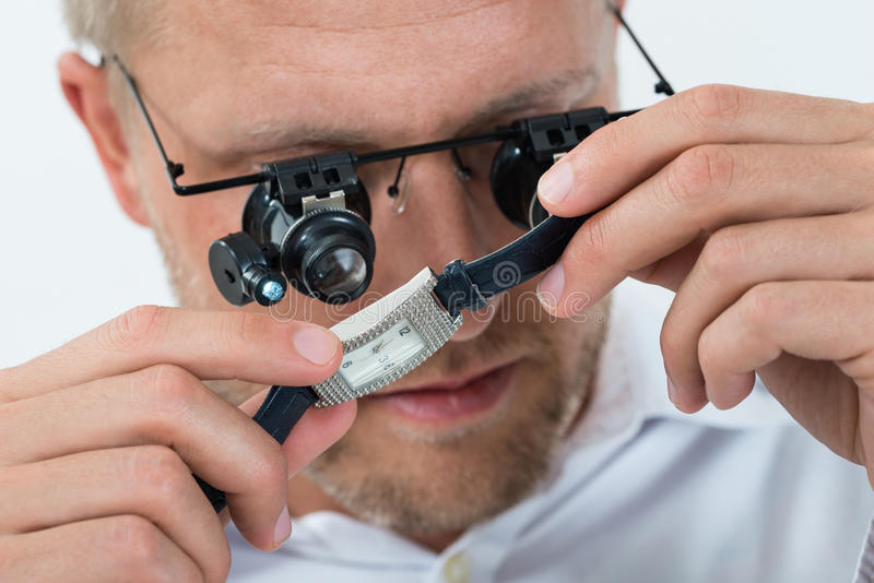 Hombre que mira el reloj con la lupa fotos de archivo libres de regalías