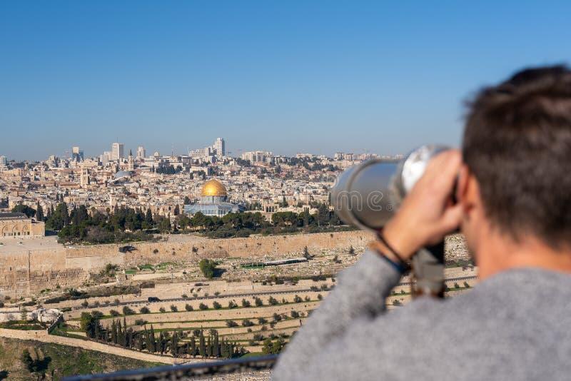 Hombre que mira la ciudad vieja de Jerusalén con un binocular imagenes de archivo