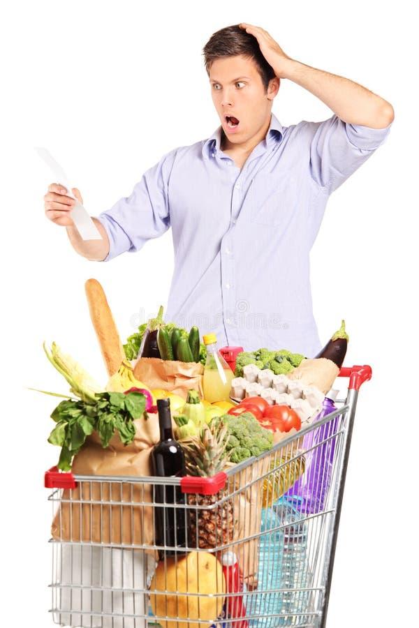 Hombre que mira la cuenta de las compras con incredulidad imagen de archivo