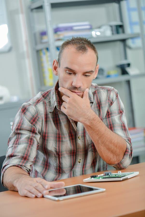 Hombre que mira la expresión preocupada tableta fotos de archivo libres de regalías