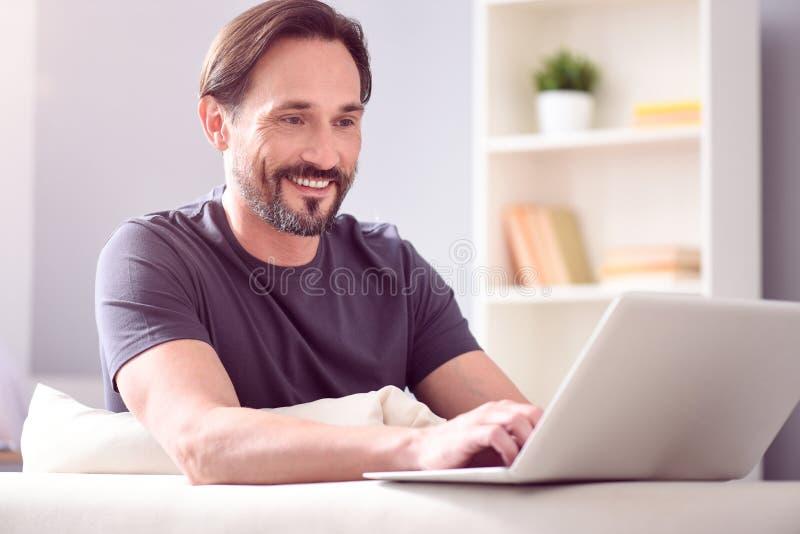 Hombre que mira la pantalla del ordenador portátil foto de archivo libre de regalías