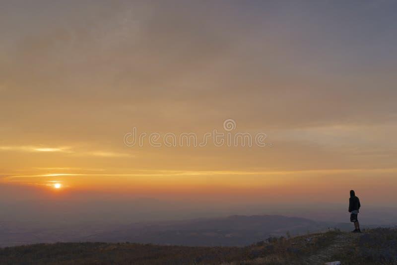 Hombre que mira la puesta del sol en una montaña fotografía de archivo libre de regalías