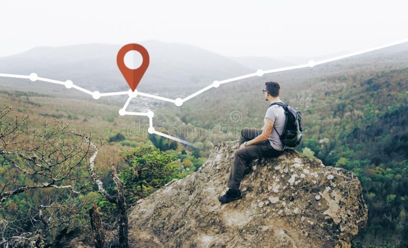 Hombre que mira la ruta con el perno de GPS en las montañas imágenes de archivo libres de regalías