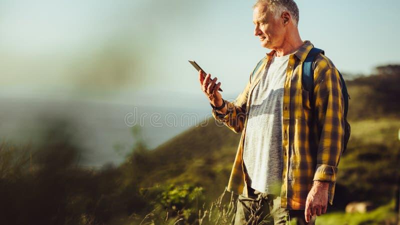 Hombre que mira la situación del teléfono móvil en una colina fotos de archivo libres de regalías