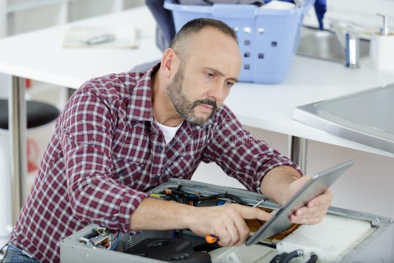 Hombre que mira la tableta mientras que intenta reparar la lavadora foto de archivo libre de regalías