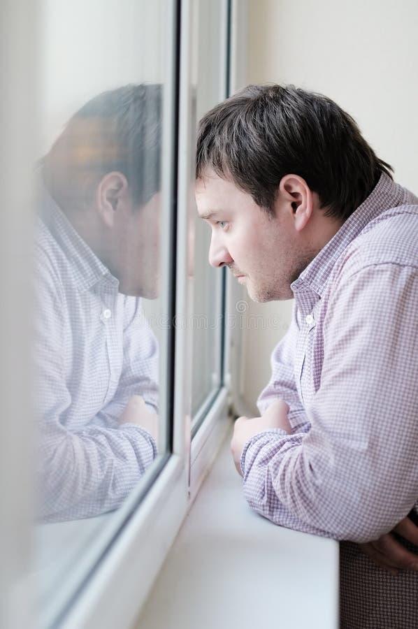 Hombre que mira la ventana imagen de archivo libre de regalías