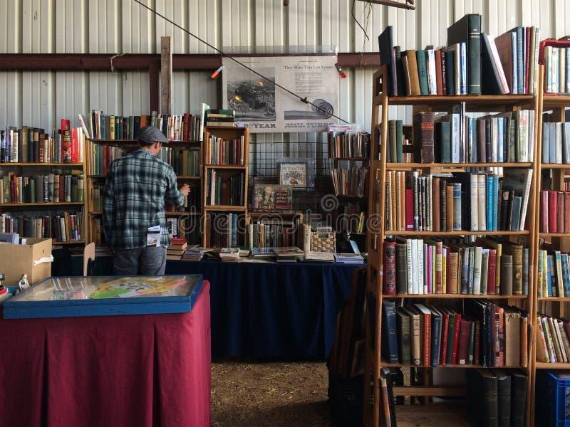 Hombre que mira los libros en tienda imagenes de archivo
