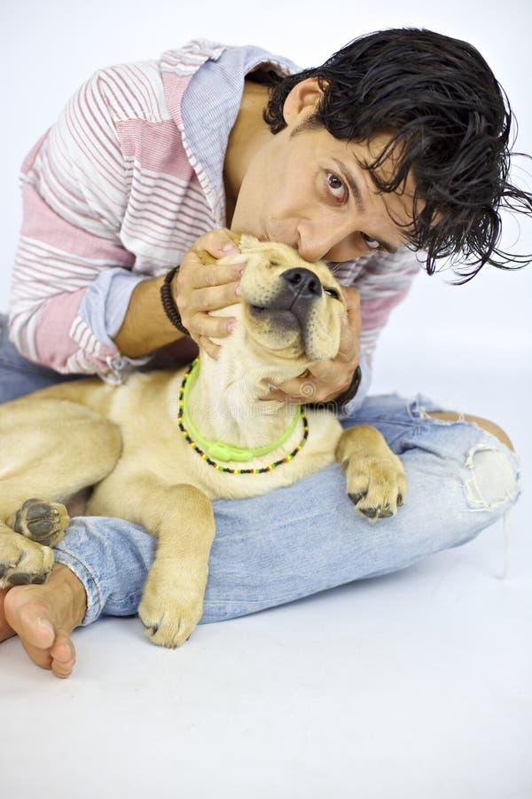 Hombre que mira mientras que besa su perro de perrito foto de archivo