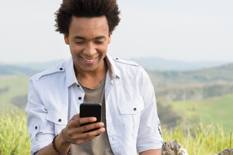 Hombre que mira que mecanografía en el teléfono imagen de archivo