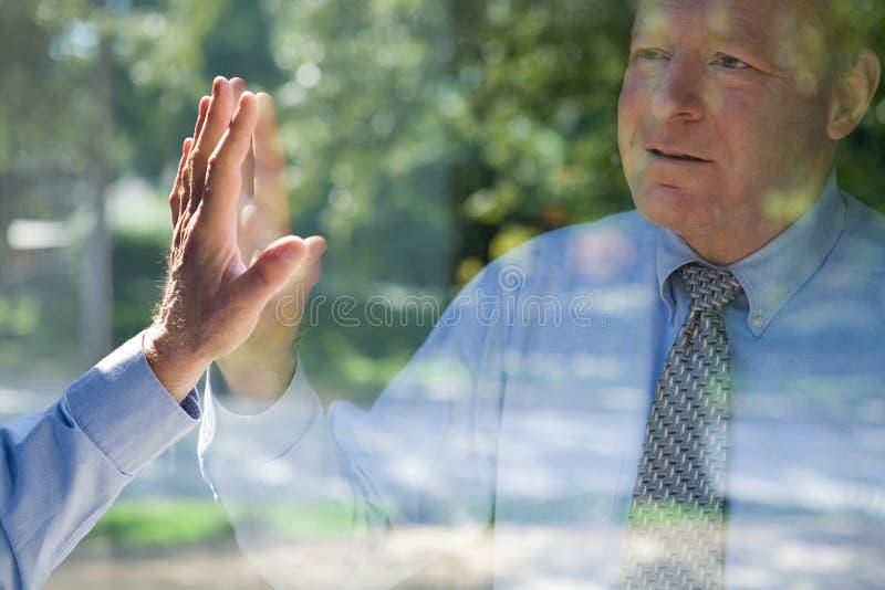 Hombre que mira su reflexión fotos de archivo