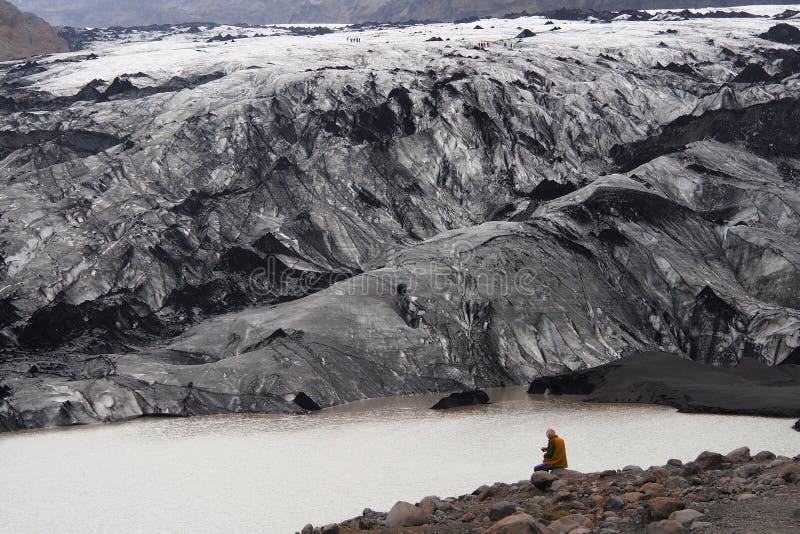 Hombre que mira un glaciar en Islandia imágenes de archivo libres de regalías