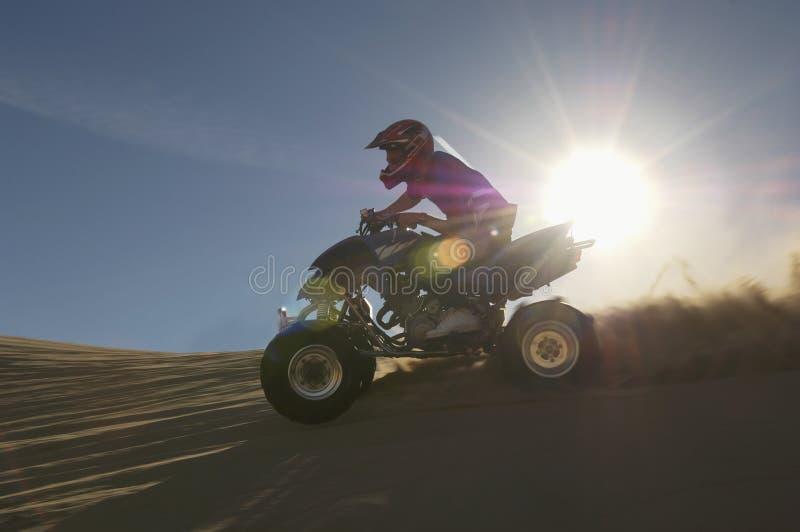 Hombre que monta Quadbike en desierto foto de archivo