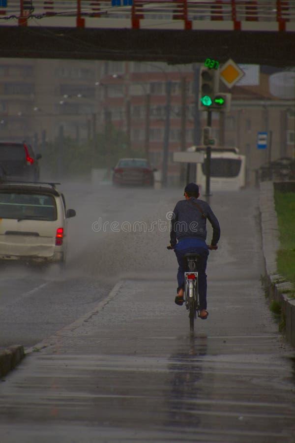 Hombre que monta una bici en la lluvia de colada imagenes de archivo