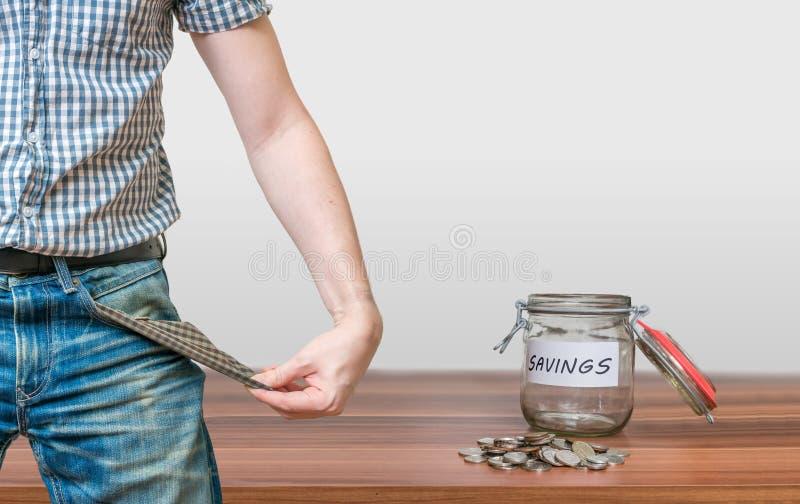 Hombre que muestra el bolsillo como ningún símbolo del dinero y el tarro con las monedas fotografía de archivo libre de regalías