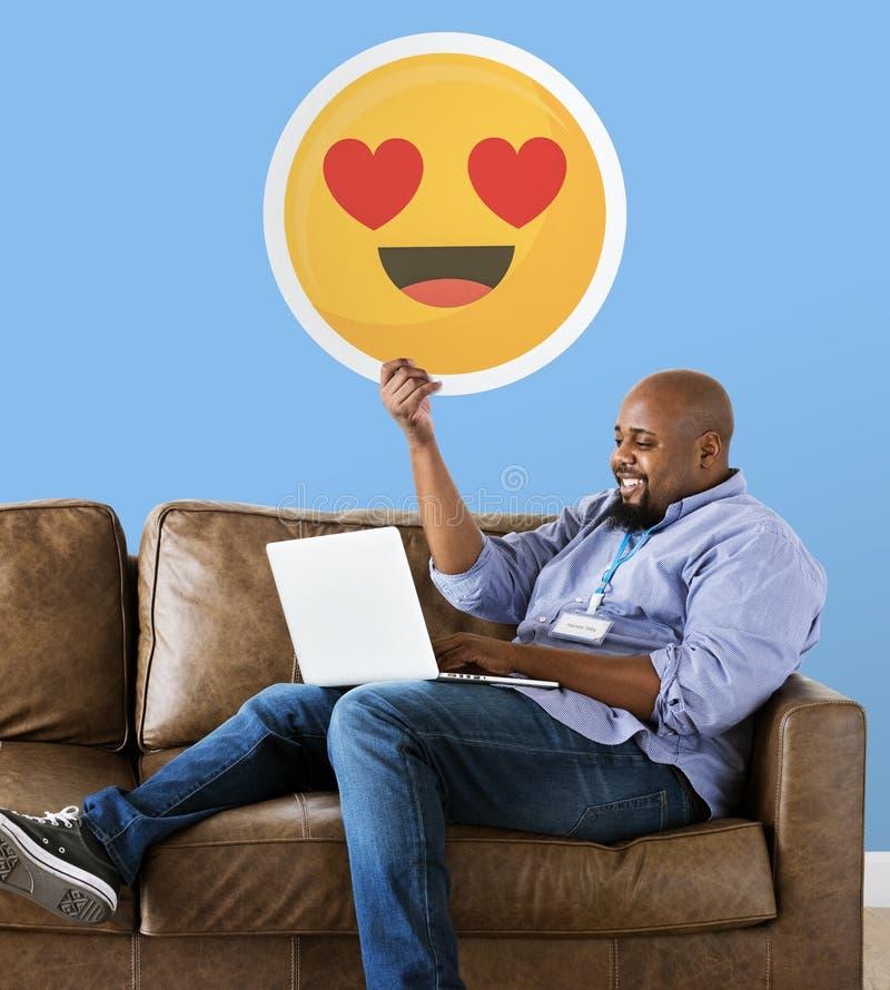 Hombre que muestra el emoticon de los ojos del corazón en el sofá fotos de archivo