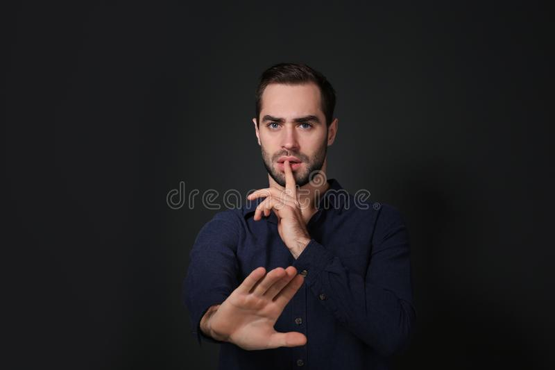 Hombre que muestra gesto del SILENCIO en lenguaje de signos en negro foto de archivo libre de regalías