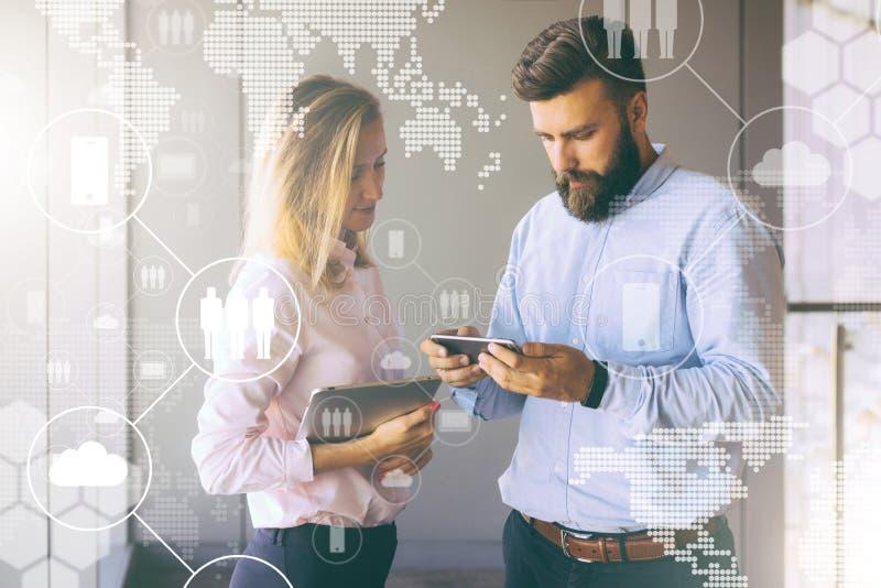 Hombre que muestra la información de la mujer sobre smartphone Muchacha que sostiene la tableta Trabajo en equipo businesspeople foto de archivo
